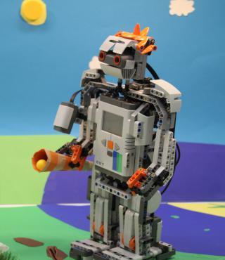 Vor einer bunten Papierkulisse, die Rasen eine Sonne und Wolken andeutet, steht ein Legoroboter.