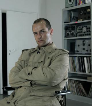 Der Wissenschaftler und Komponist Marcus Schmickler sitzt mit vor der Brust verschränkten Armen vor einem Regal mit Schallplatten und elektrischen Geräten