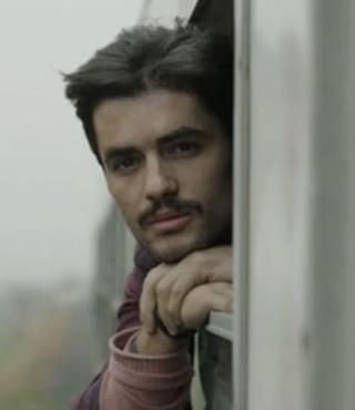 Filmstill aus »Zer«: Ein junger Mann schaut aus dem Zug.