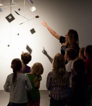 im dunkeln stehende Kinder betrachten ein Mobile, das vom Licht angestrahlt wird