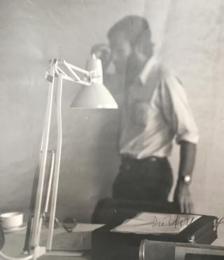 A black and white photograph shows sharply a desk lamp in the foreground. In the background one is out of focus a man with a beard and a white shirt.