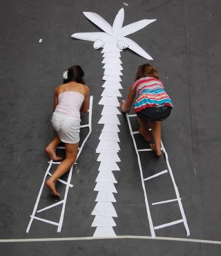 Two girls climbing on paper ladders a paper palm tree