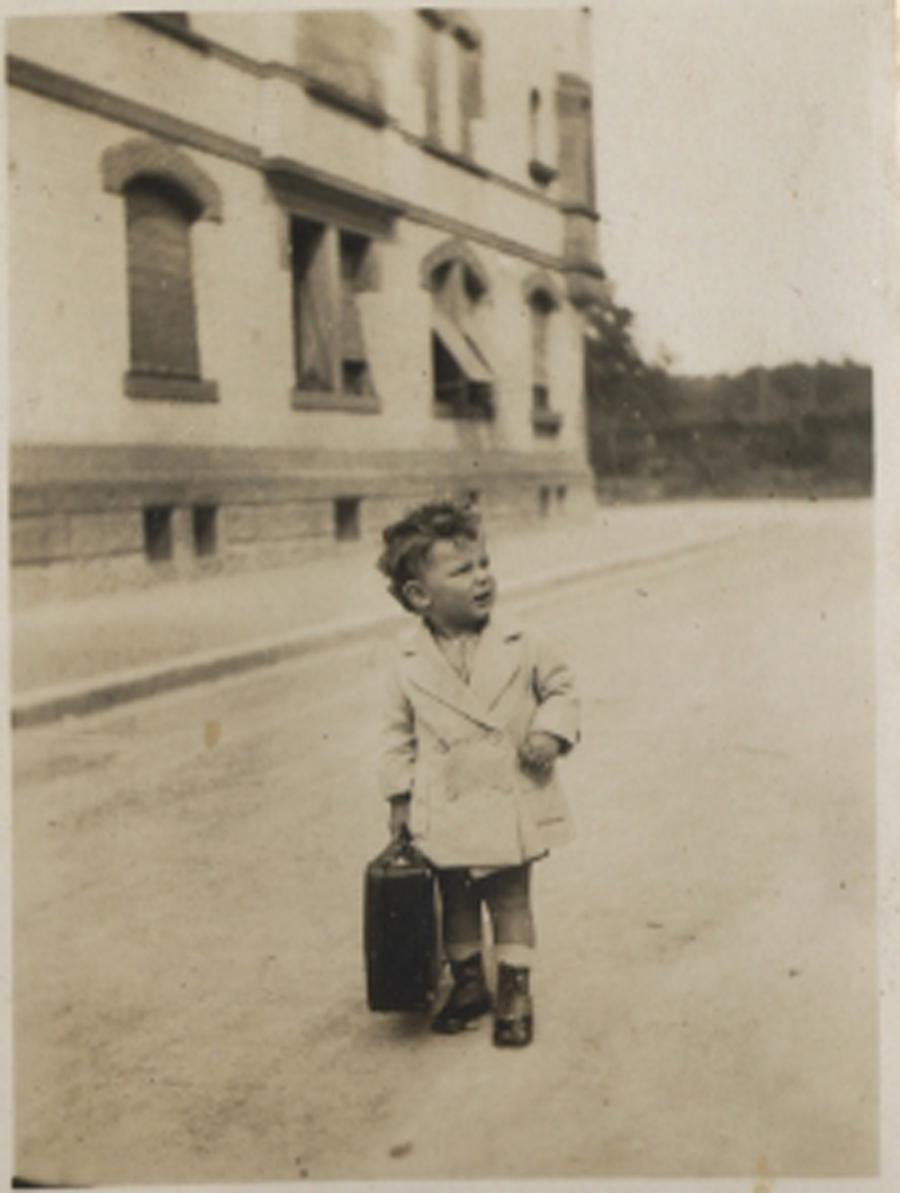 Kleiner Junge mit Koffer vor Hausfassade.