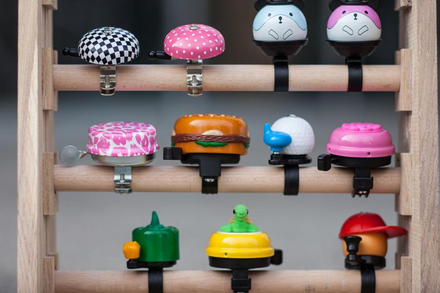 A shelf full of colorful, different bicycle bells