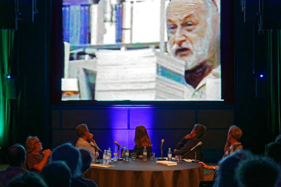 Die Diskussionsteilnehmer blicken auf eine Projektionsleinwand hinter ihnen, die ein Video mit Vilém Flusser zeigt.