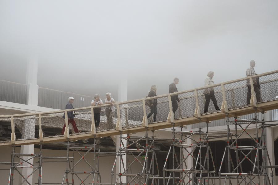 People walking via a ramp into a cloud