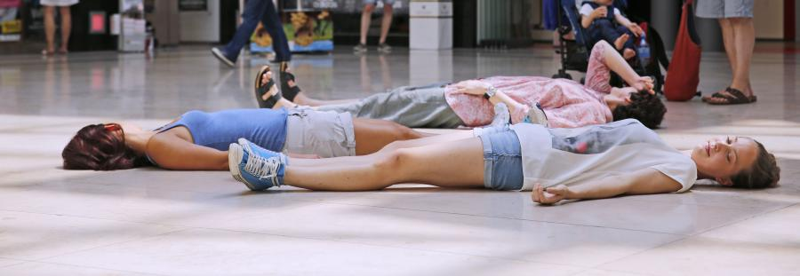 Three persons lay on their back on the ground