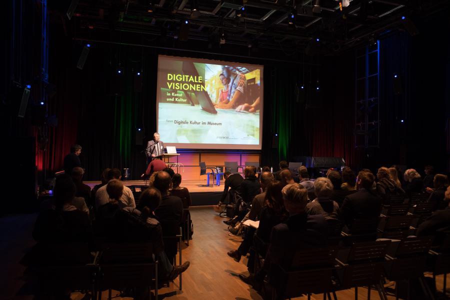 Ein mit Menschen gefüllter Saal und ein Mann auf der Bühne, der einen Vortrag hält.