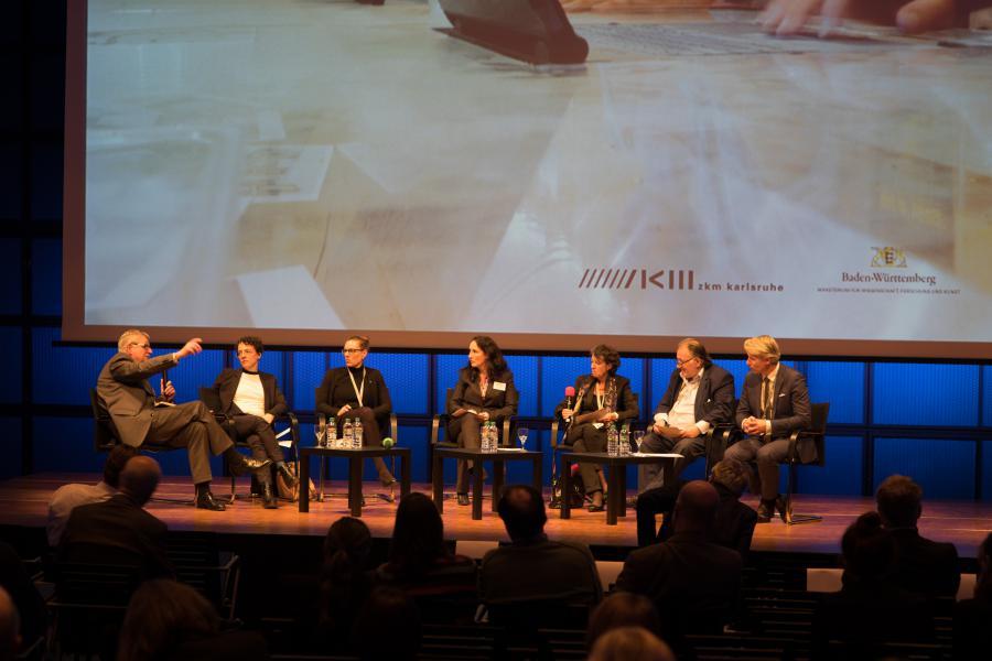 Sieben Personen sitzen in einem Halbkreis auf einer Bühne und diskutieren.