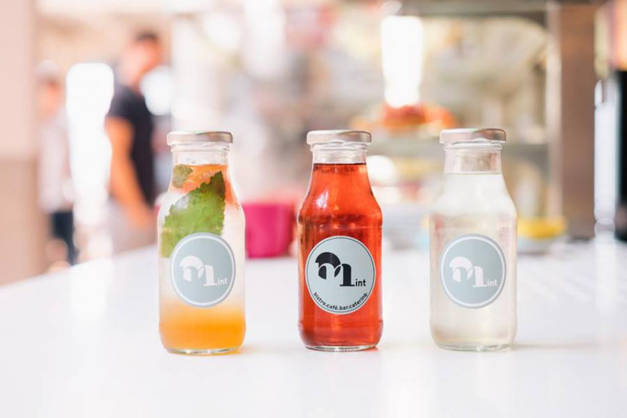 three small glass bottles with colored drinks