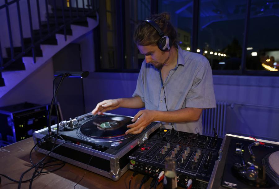 Ein Mann mit Kopfhörern legt eine Platte auf.