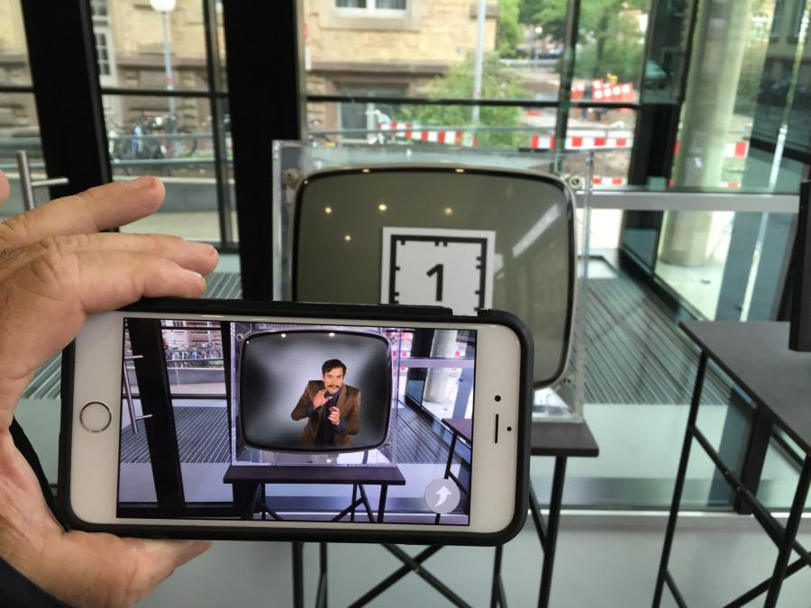 A smartphone is helt to catch the augmented reality marker glued on a cathode ray tube TV.