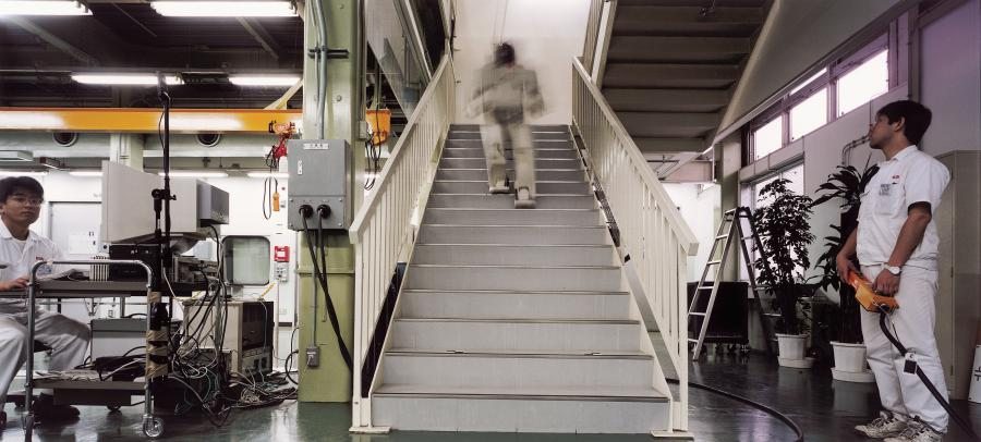 A robot walking up the stairs in an industrial building