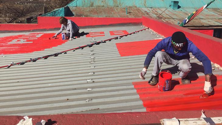 """Personen malen das Wort """"One"""" auf ein Dach"""