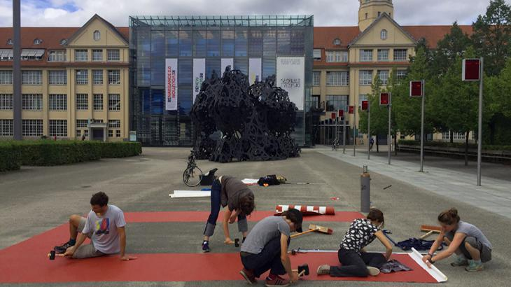 """People drawing the word """"unites"""" on a the ZKM_Forecourt"""