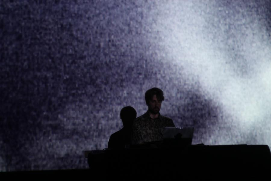 Man on stage in front of a laptop. Background dipped in white light