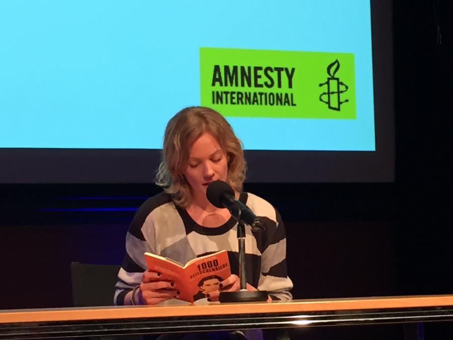Eine Frau sitzt am Tisch und liest aus einem Buch