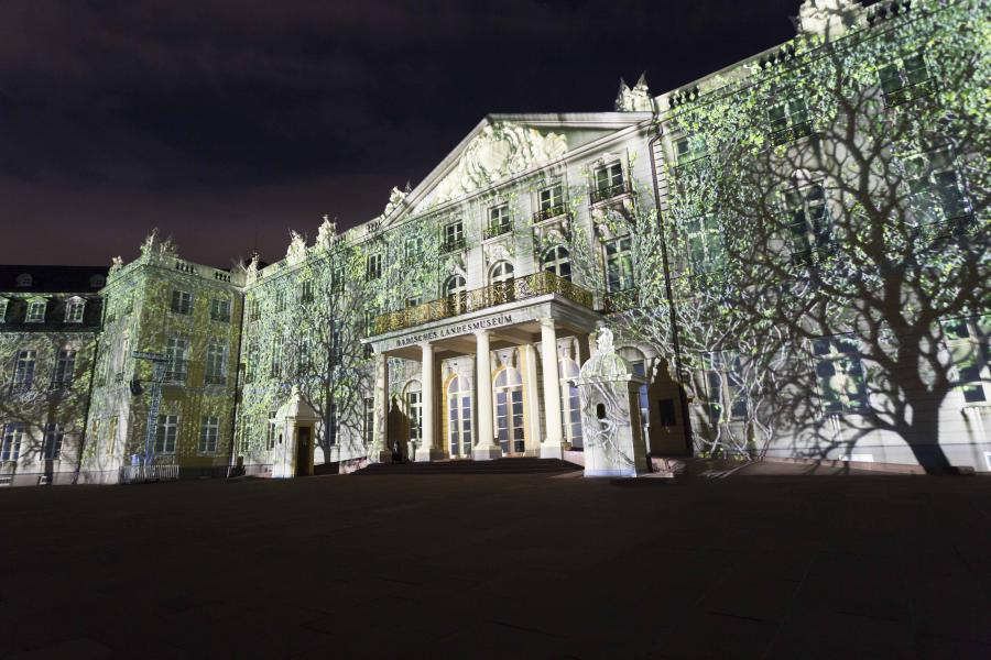 Projected green trees on the palace facade