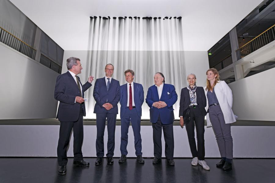 Four men and two women standing in front of an installation that represents a kind of curtain of oil.