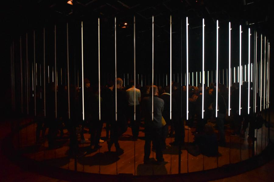 A circle of glowing neon tubes, many people standing in it