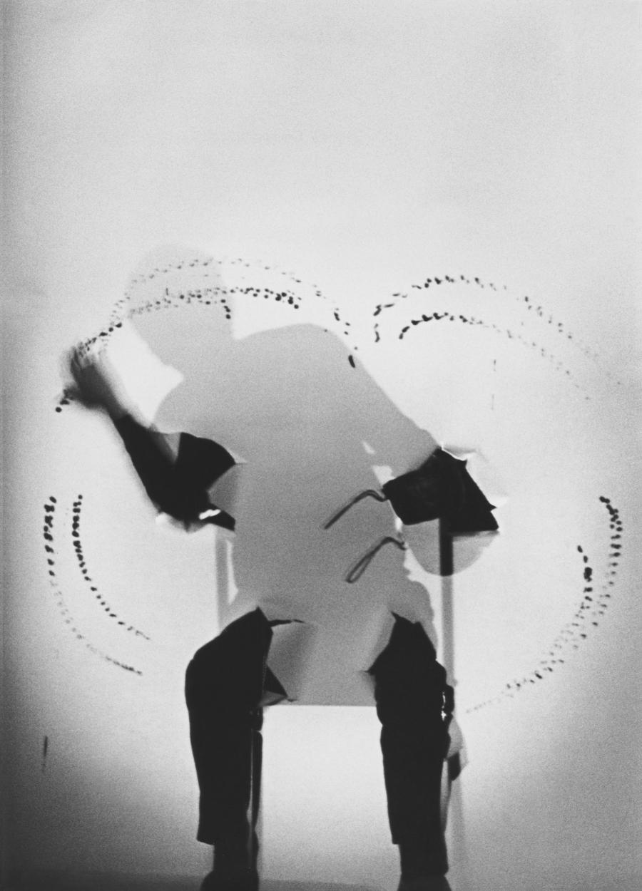 Schwarz-weiß Bild einer Silhouette, die auf einem Stuhl sitzt