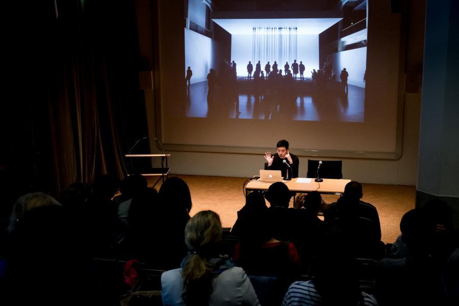 Ein Mann sitzt am Tisch und spricht zum Publikum. Im Hintergrund ein Bild mit schwarzen Rinnsalen.
