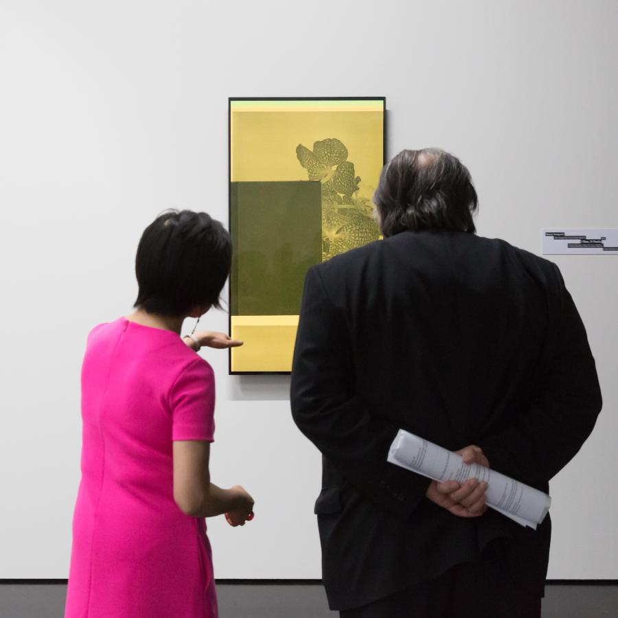 Two persons stand in front of a hanging picture