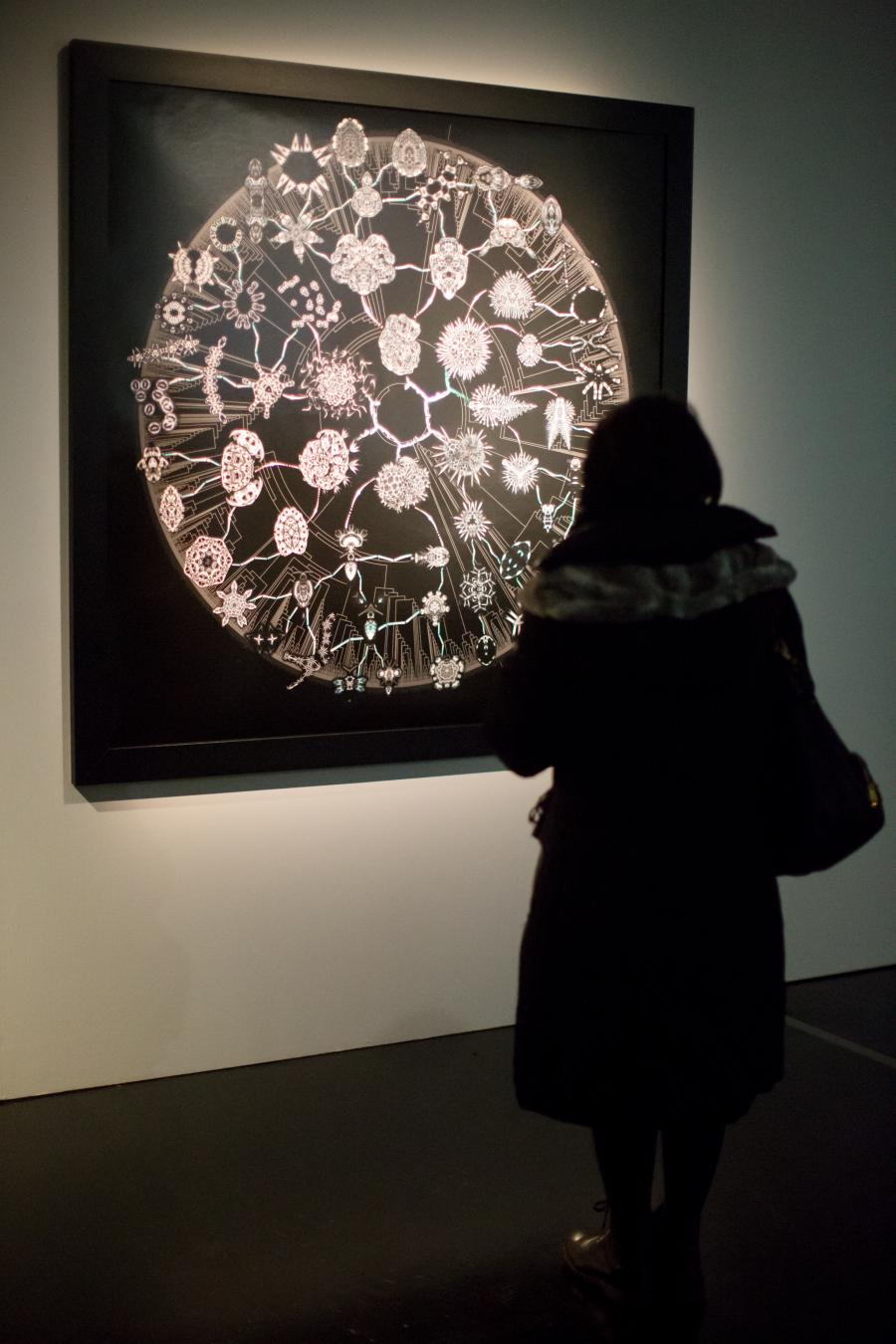 A woman stands in front of a luminous picture