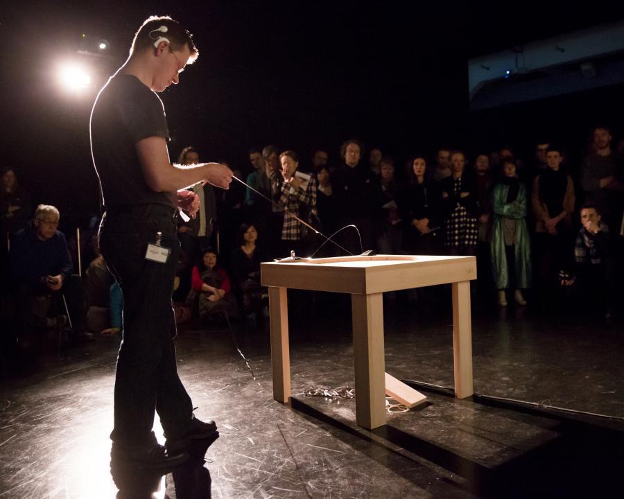 Ein Mann steht vor einem Tisch und hält einen Bindfaden in der Hand