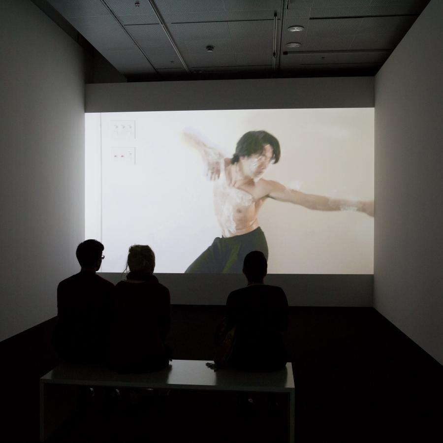 Three persons sit in front of a screen on which a man, wrapped in cling film, can be seen