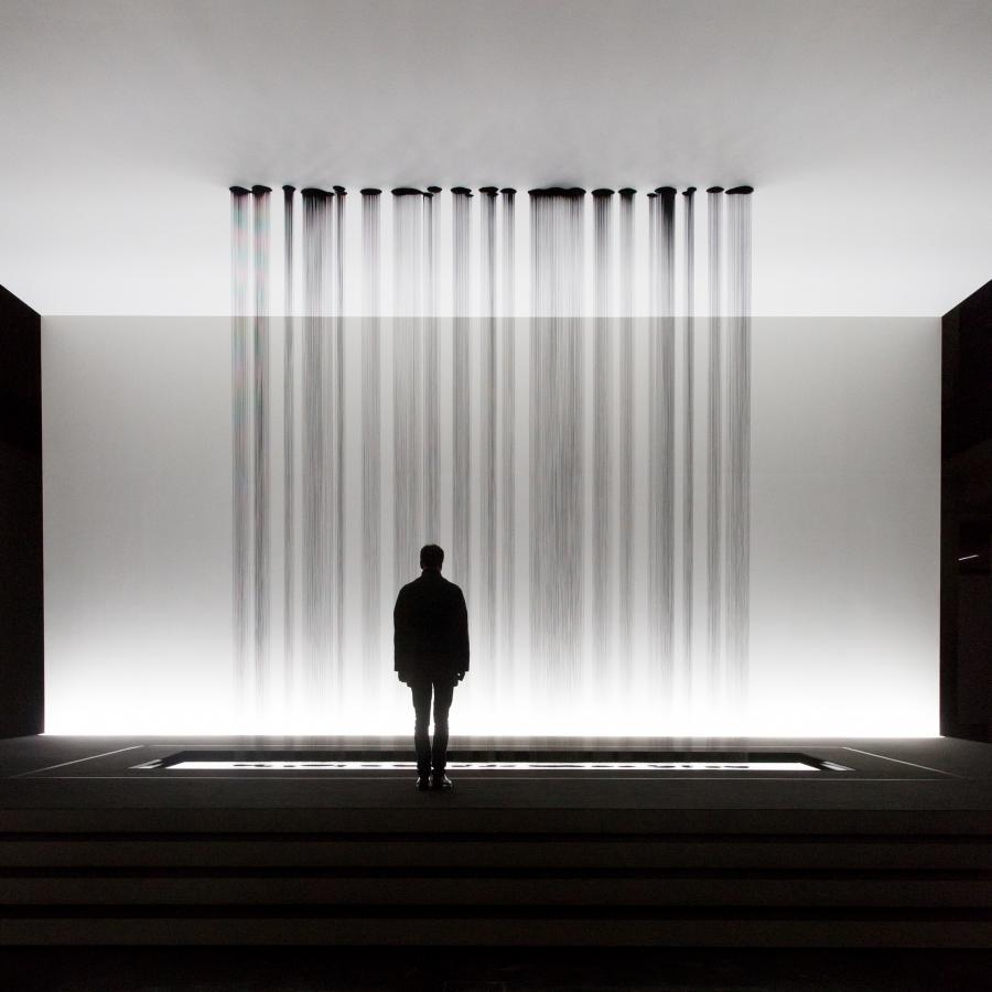 A person stands in front of a sculpture, at the drop several rivulets of oil on the floor