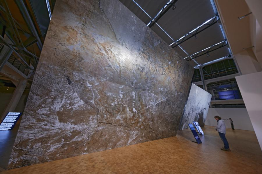 A person standing in front of a huge canvas on which a total of a cracked ground can be seen