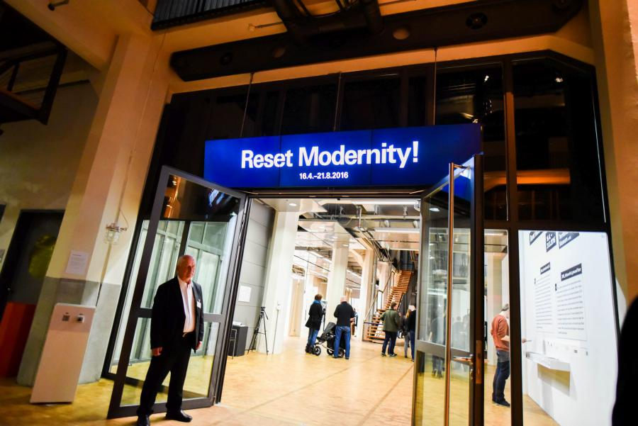 neon sign above a door with words »Reset Modernity!«