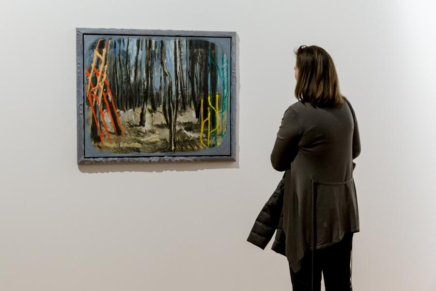 The picture shows a woman in front of a painting by Markus Lüperz