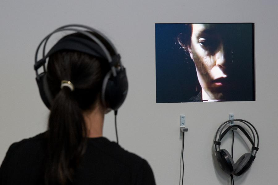A woman with headphones is watching a video of another woman.