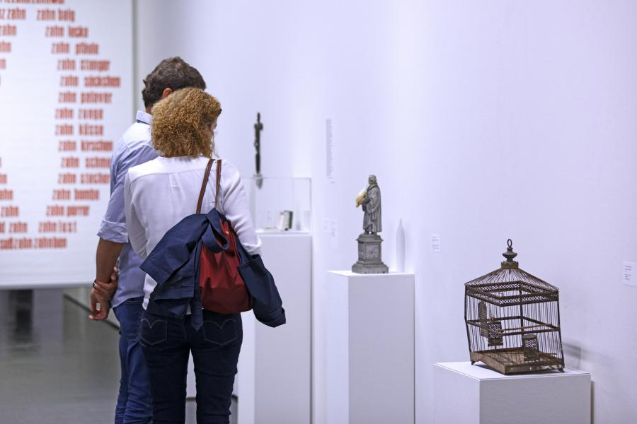 The photo shows visitors in front of artworks by Konrad Balder Schäuffelen