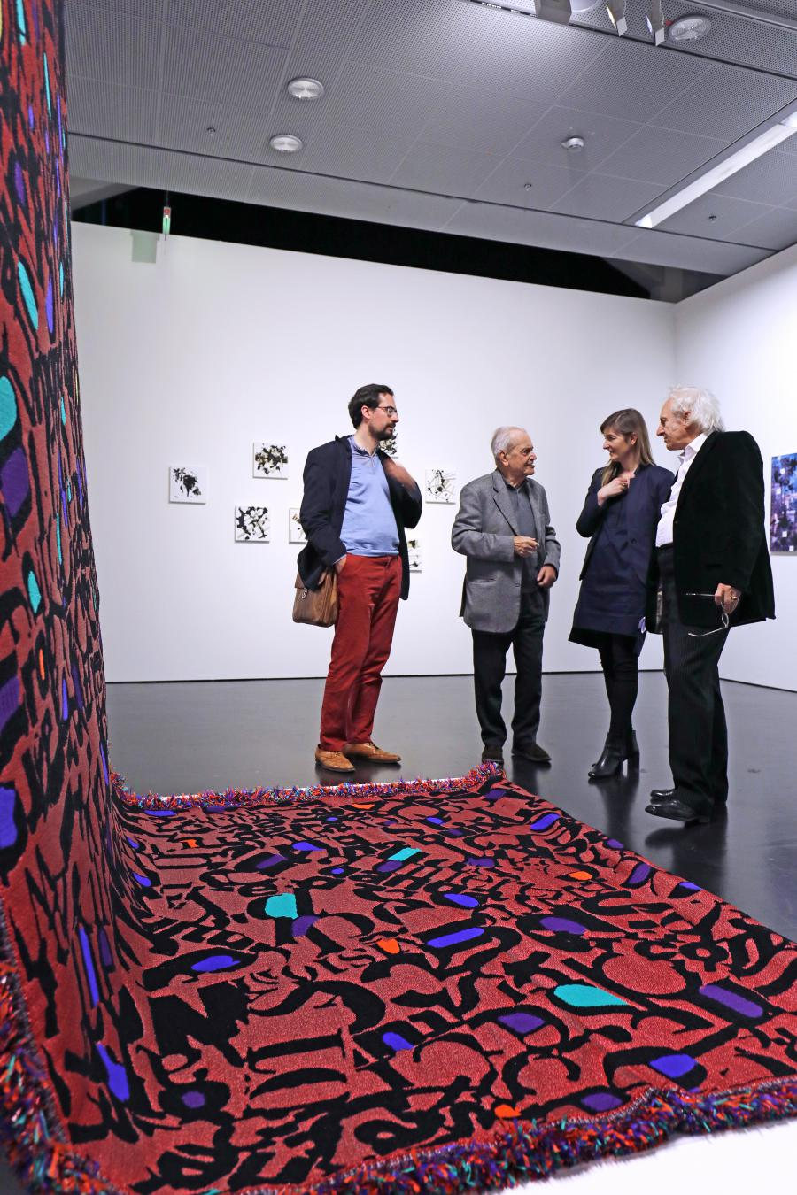 Four people are standing in front of an artwork which is a red carpet wih letters on it.
