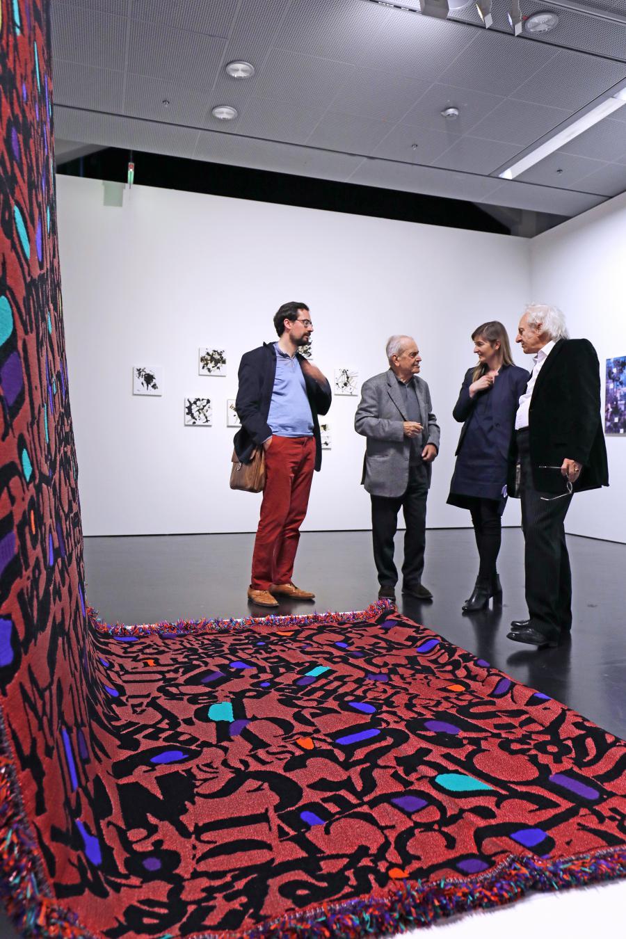 Vier Menschen stehen vor einem Werk, das aus einem langen roten Teppich mit Buchstaben besteht.