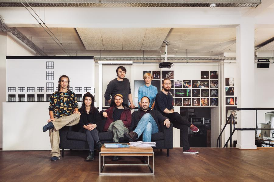 Das Künstlerkollektiv sitzt auf einem Sofa in ihrem Studio