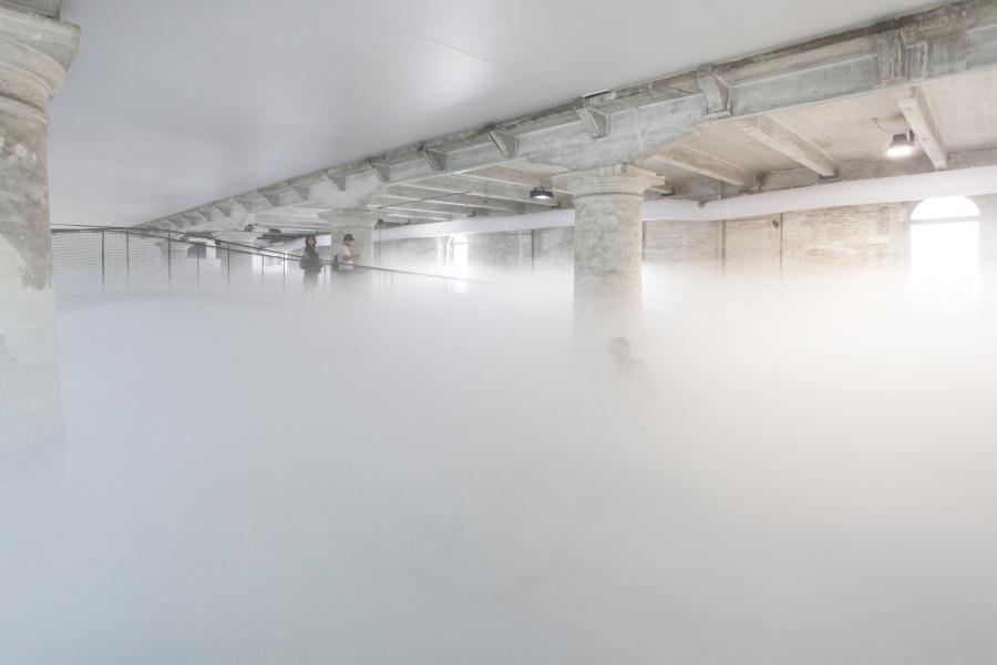 People walk through an artificial cloud via a ramp.