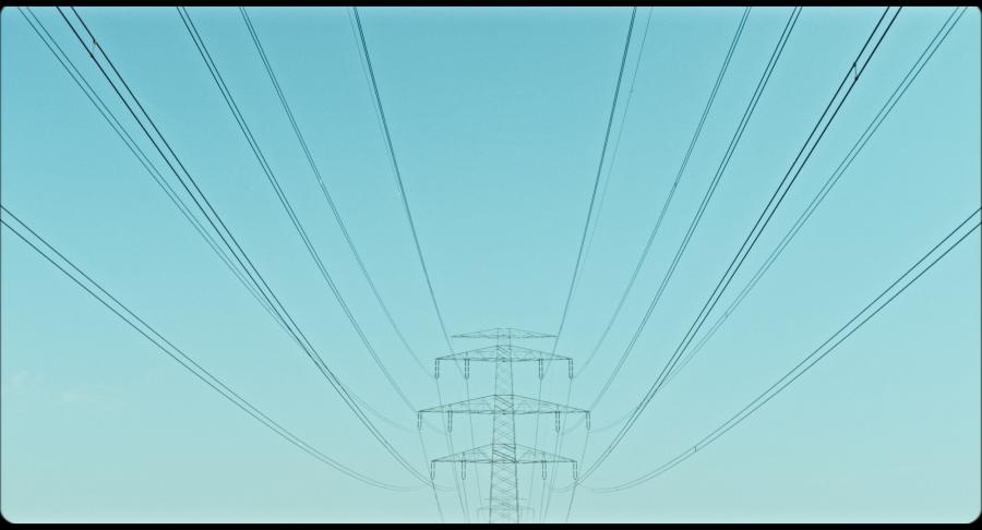 Das Bild zeigt einen Strommast vor einem türkisblauen Himmel.