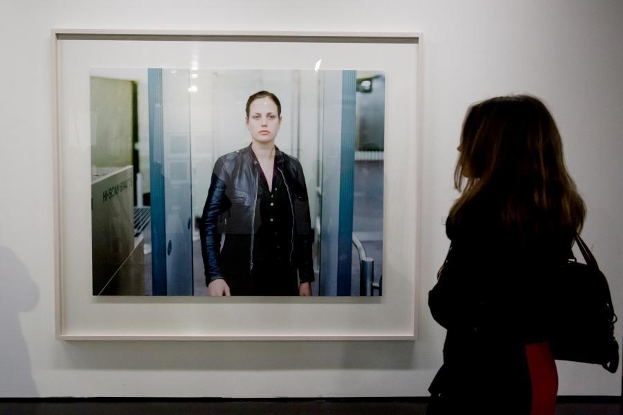Eine Frau steht vor einer Fotografie