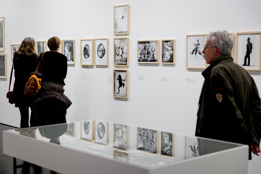 Two women and a man walk past walls with pictures