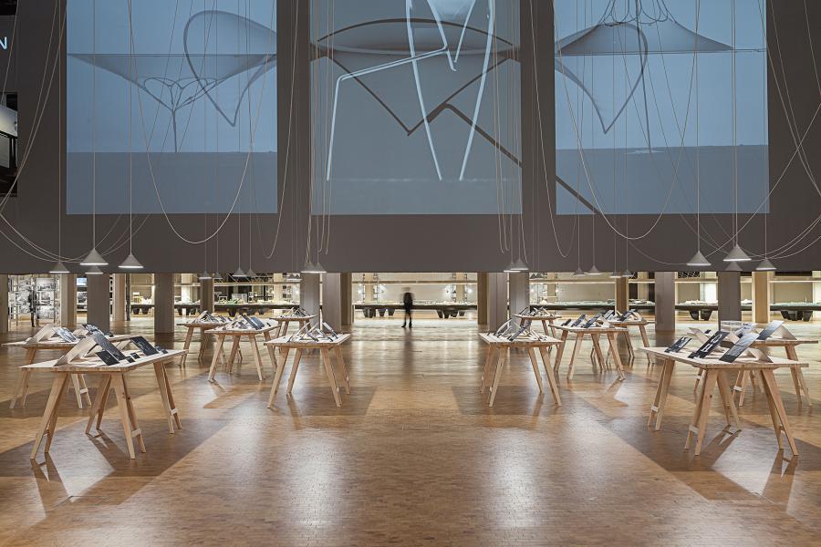 Frei Otto Ausstellungsansicht: Tische mit Schwarzweißfotos, hängenden Seilen und einem raumfüllenden Screen