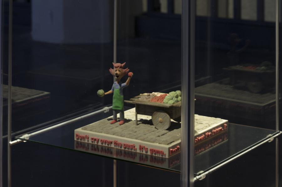 A small kneaded fox stands on a pedestal in a display case
