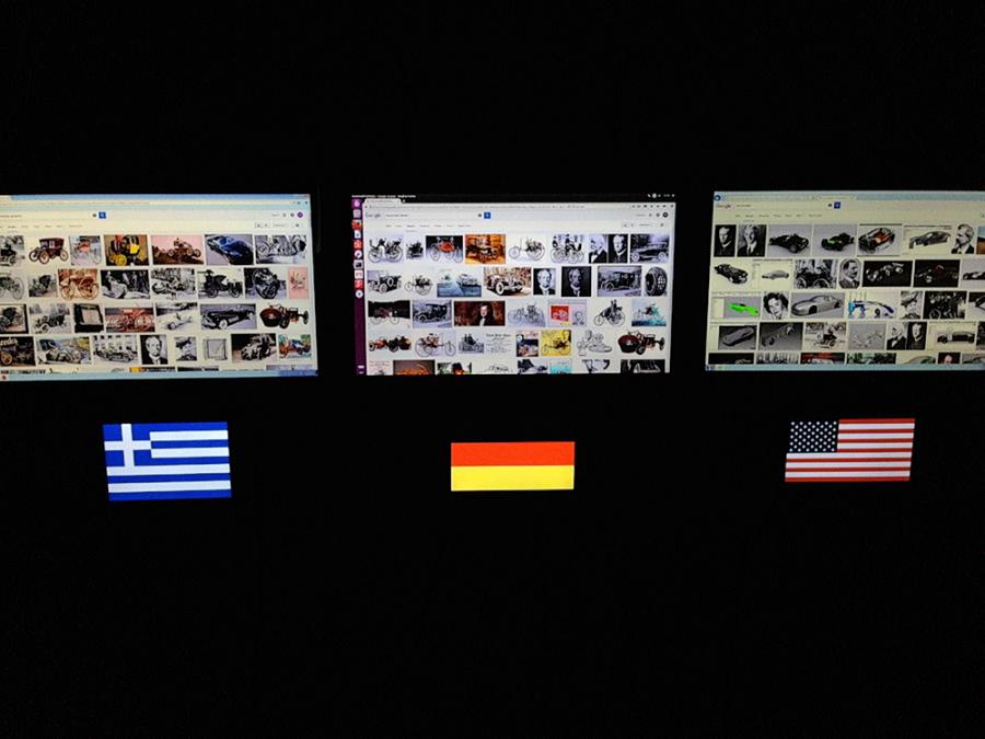 Drei Bildschirme mit unterschiedlichen Anzeigen; darunter die Flaggen von Griechland, Deutschland und den USA