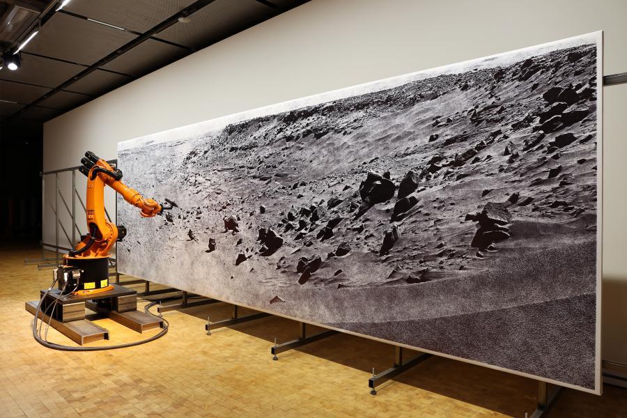Ein orangener Roboter zeichnet ein Bild einer Mondlandschaft