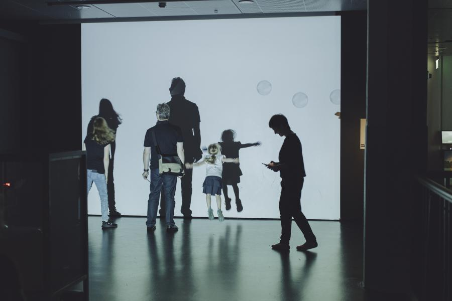 Museum visitors move in front of a canvas with soap bubbles