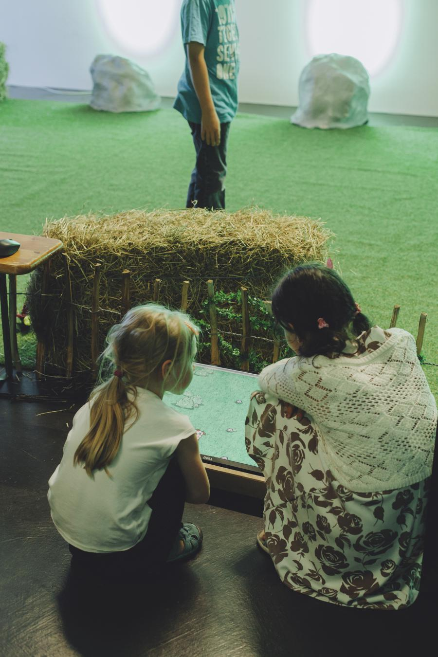 Two children sit kneeling in front of a screen