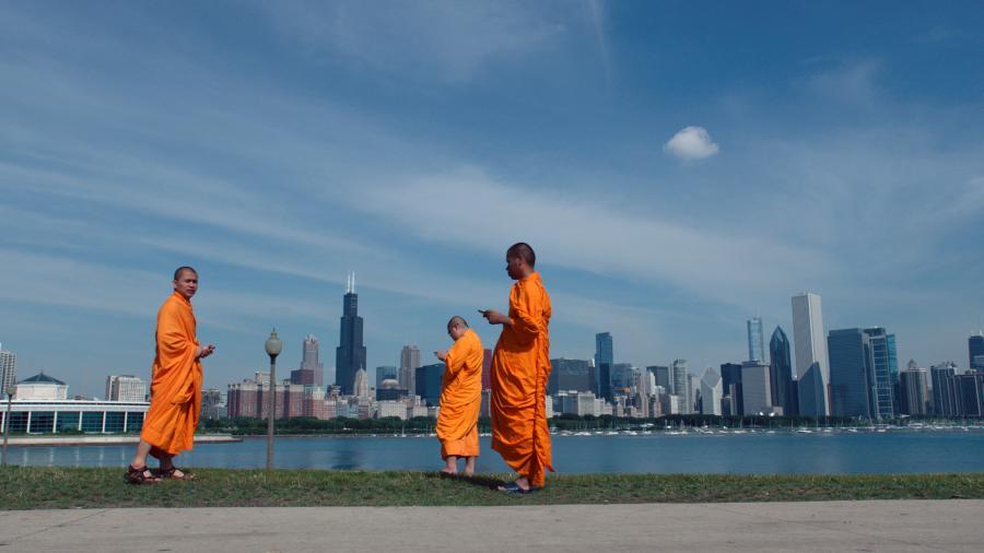 Drei Männer in tibetischer Tracht stehen vor der Uferskyline einer großen modernen Stadt. Alle drei schauen auf ihr Smartphone.